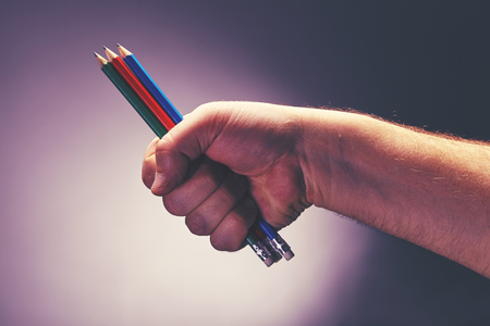 The mans hand offers several colored pencils