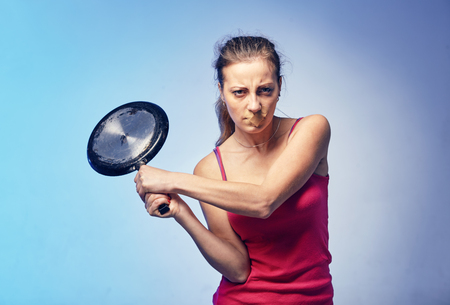 A woman with a frying pan in her arms