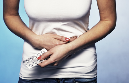 Female suffering from strong stomach ache abdominal pain.