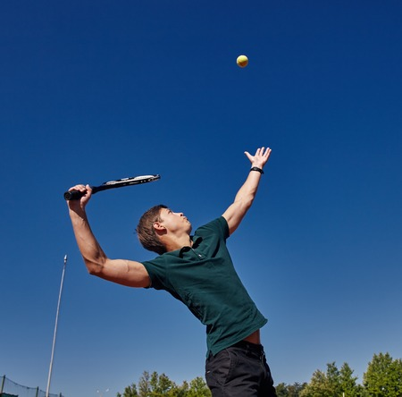 a Man playing tennis on the court on a beautiful sunny day Stock Photo