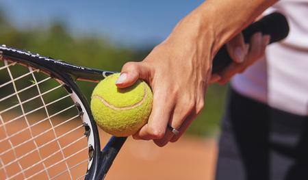 ein Tennisspieler, der Schläger und Ball in den Händen hält Standard-Bild