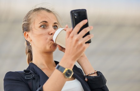 business woman drinks coffee while looking on her cell phone. She is very surprised