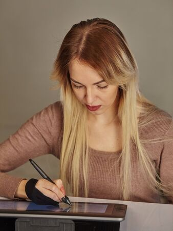 girl artist draws a digital pen on a professional tablet in her studio