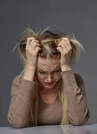 woman suffering from stress or headache while being offended by pain, Stock Photo