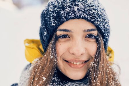 Winter portrait of young beautiful woman wearing knitted snood covered in snow. Snowing winter beauty fashion concept