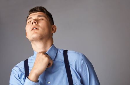 young businessman tired and trying to unbutton his shirt