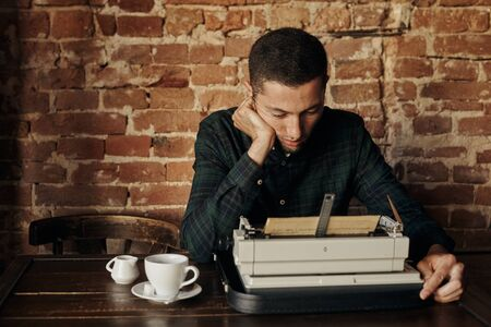 Young man writing on an old typewriter. He pondered