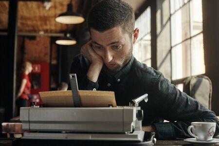 Young man writing on old typewriter.