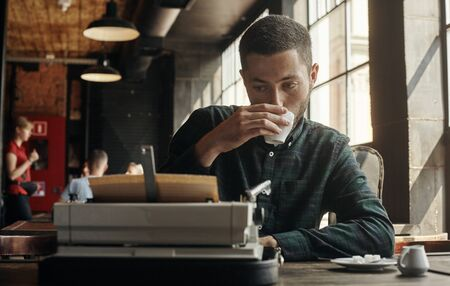 man writing on an old typewriter. In the meantime, he drinks coffee