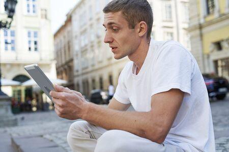 man sitting on the sidewalk uses a tablet