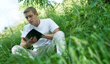 man sitting in the quiet green grass and reading a book