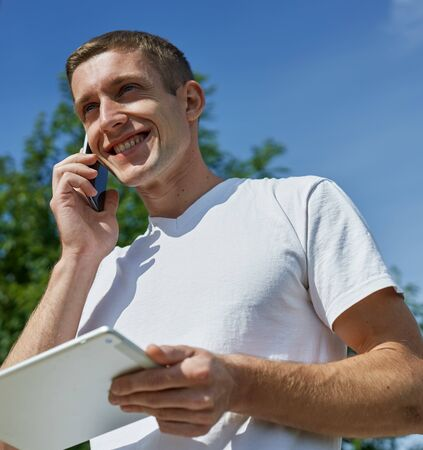 man looking at his tablet someone is calling on the phone