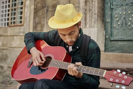 Lovely young street musician with guitar Imagens