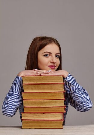 young business woman with stack of books she wants to study