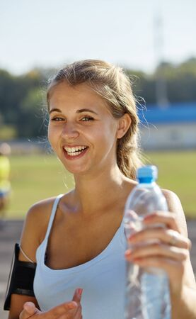 Sporty woman drinking water against the stadium. Фото со стока