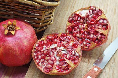 canastas con frutas: Granadas maduras reducido a la mitad en una tabla de madera