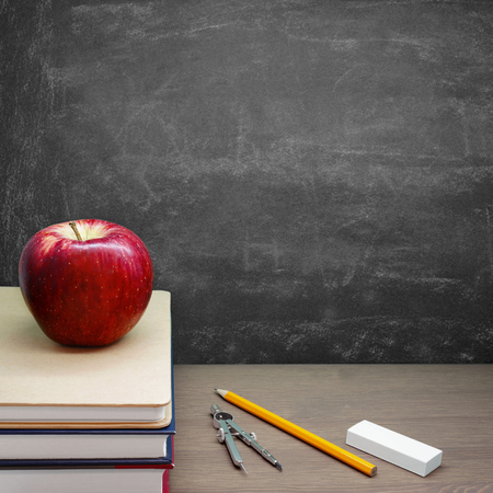Back To School  A Red Apple on a Pile of Books in front of a Chalkboard