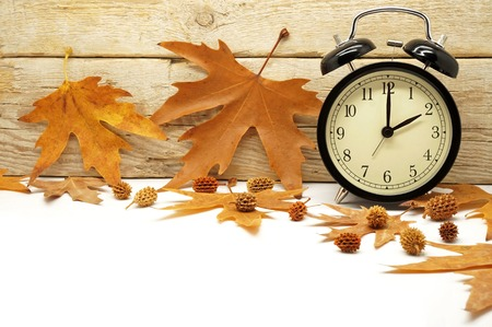 clock: Autumn Time Change  Fall Back  Maple Leaves and an Alarm Clock on a Wooden Background