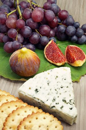 accompanied: Blue Cheese Accompanied by Figs, Grapes and Saltine Crackers on a Wooden Platter