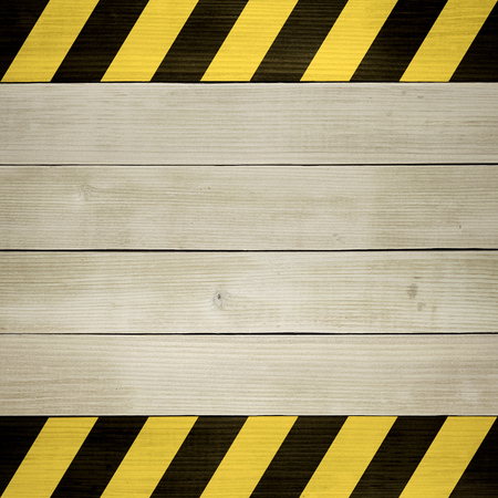 hazard stripes: Under Construction - Wooden Background Painted with Black and Yellow Hazard Stripes