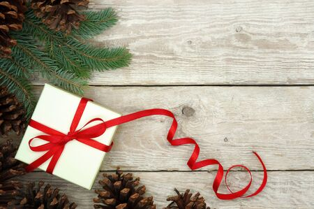 red ribbon bow: Christmas Present Wrapped with Red Ribbon on a Wooden Background Decorated with Fir Cones and Branches