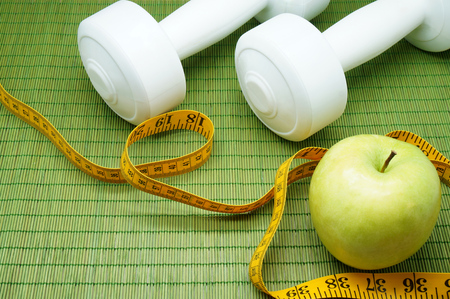 get a workout: Time for Exercise and Diet - An Apple, a Measure Tape and Two Dumbbells on a Green Mat