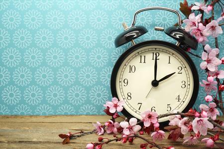 春の時間変更 - ピンク色の花と古い木製テーブルの上の目覚まし時計