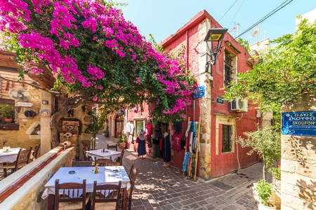 CHANIA, GREECE - AUGUST 23, 2017: Cobblestone Street in Chania Old Town Covered with a Blooming Bougainvillea. 新闻类图片