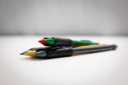 different colored pencils on a white background