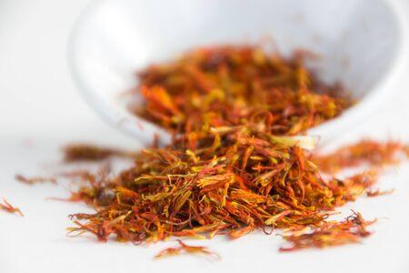 intense flavor: saffron in a white bowl on white background