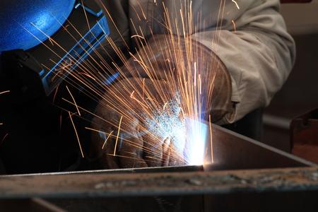 soldadura: Pieza de acero de soldadura soldador MIG con todo el equipo de seguridad Foto de archivo