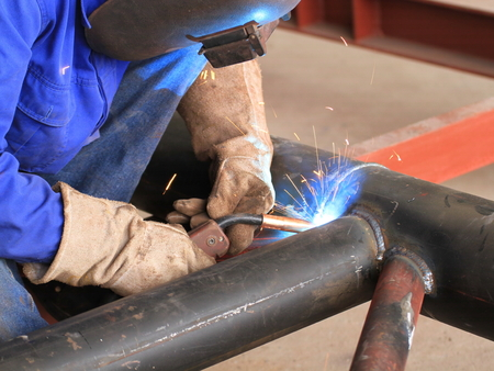 welding mask: welder is welding pipe structure with all safety, Shown good welds Stock Photo