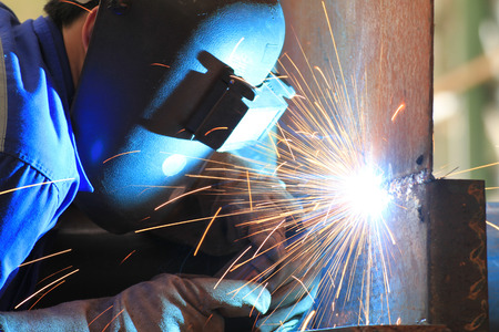 welds: welder is welding chekered plate with all safety in factory