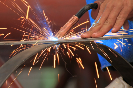 welds: welder is welding steel flat bar without safety glove Stock Photo
