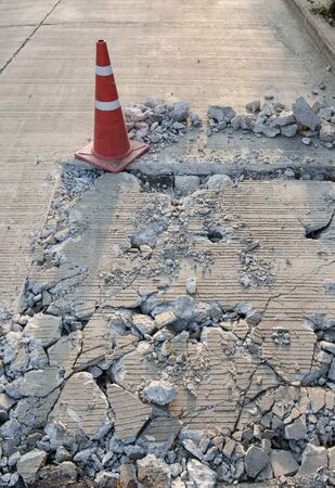 damage with cracks at street with traffic cone photo