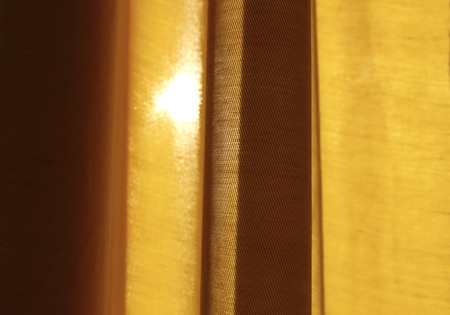 Sunlight coming through the old yellow curtain Stock Photo