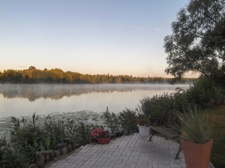 Early morning on the river Bank. A place to relax, well-maintained coast of a country house.