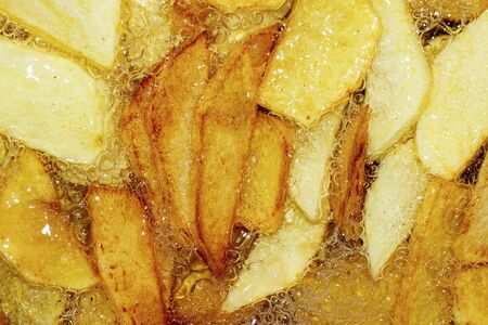 Cooking French fries. Close-up of frying French fries in a deep fryer in hot boiling oil.