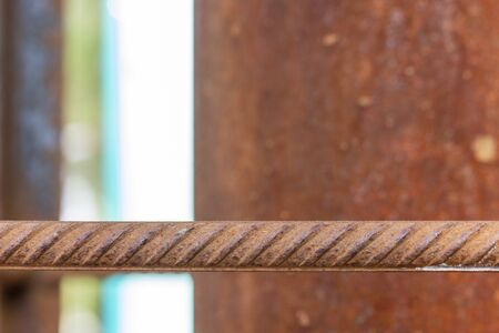 macro of corrosion-textured vintage rusty metal pole, rusty metal fence close-up sunlit.