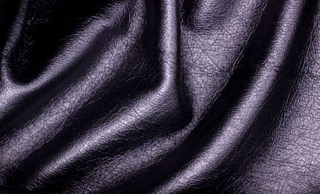 Black artificial skin close-up. Textile material, sloppy folds. Black leather background