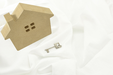 lodgings: wood model of house as symbol with key on white fabric background