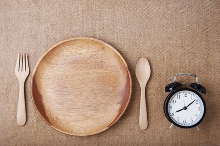 Top view : Empty wood plate with spoon and fock and alarm clock on brown sackcloth. Alarm clock remind eat breakfast. Diet time with empty food on wood plate. proper nutrition, discipline,  adhere to diet time. Empty foods at breakfast concept.