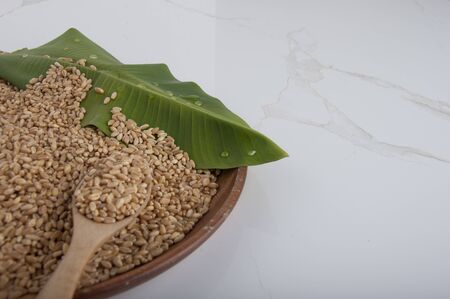 wheat grain on plate with banana leaf. Natural food healthy with wheat seed. Wheat gain put on the plate. Wheat on white marble tile background. Zdjęcie Seryjne