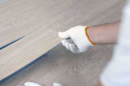 Worker installing wood plank for new room. Home renovation with vinyl wood floor Installation for home decoration with laminate vinyl wood floor.  Фото со стока