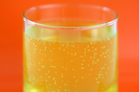 effervescent: A glass of orange flavored calcium effervescent tablet dissolving in water  Stock Photo