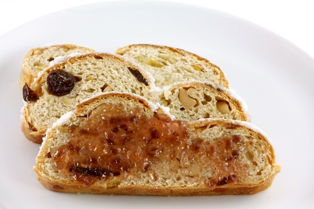 Sweet Jam on a  slice of homemade Christmas stollen cake with raisins, nuts, spices and chopped dried fruit photo