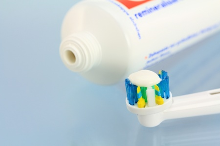 Toothpaste and a new electric toothbrush head on a shiny blue background Stock Photo - 12581783