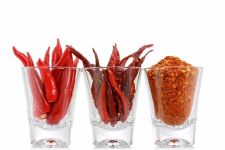 pimientos: Tres versiones de Red Chili Pepper frescos, secos chile en polvo y chile en un espejo, aislado en fondo blanco