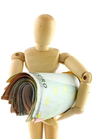 marioneta de madera: Un muñeco de madera que sostiene un rollo de papel moneda, la moneda con fuerza Foto de archivo