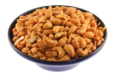 Closeup photo of a bowl full of Roasted and Salted Cashew Nuts  isolated on white